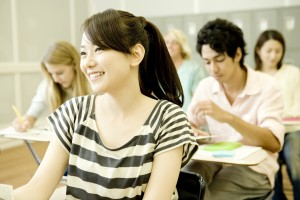smiling female student  studying in classroom